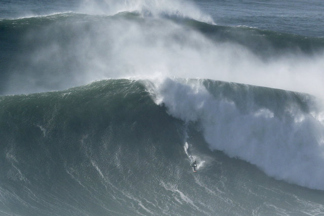 A surfer drops down a wave during a tow surfing session at Praia do Norte or North Beach in Nazare, Portugal, Thursday, October 29, 2020. A big swell generated earlier in the week by Hurricane Epsilon in the North Atlantic, reached the Portuguese west coast drawing big wave surfers to Nazare. (Photo by Pedro Rocha/AP Photo)