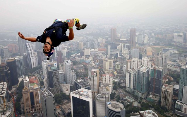 Base jumper Vincent Philippe Benjamin Reffet from France leaps from the 300-metres Open Deck of the Malaysia's landmark Kuala Lumpur Tower during the International Tower Jump in Kuala Lumpur on September 27, 2013. (Photo by Mohd Rasfan/AFP Photo)