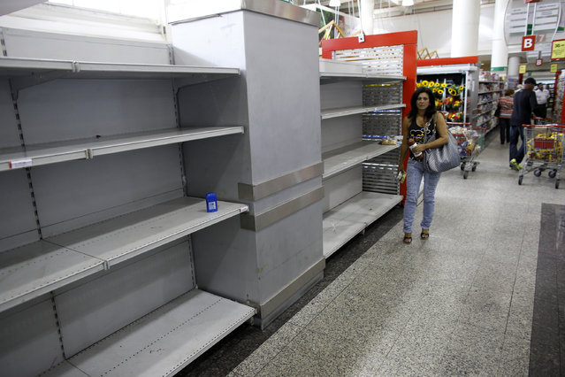A woman walks past an empty section where toilet paper should be on display in a super market in Caracas, May 17, 2013. (Photo by Jorge Silva/Reuters)