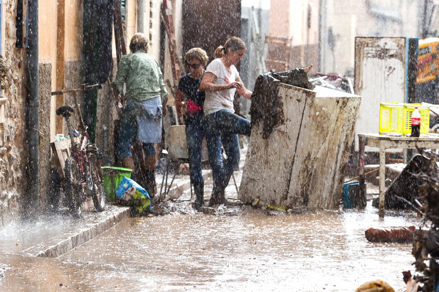 Residents place their damaged belongings on the street under pouring rain, in Sant Llorenc, 60 kilometers (40 miles) east of Mallorca's capital, Palma, Spain, Wednesday, October 10, 2018. Torrential rainstorms that caused flash flooding of water and mud on the Spanish island of Mallorca killed at least nine people, authorities said on Wednesday. (Photo by Francisco Ubilla/AP Photo)