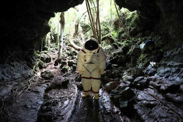 "Peter Weiss, director of the Space Department of COMEX, (c) tests a pressurized suit identical to those used in space expeditions in the lava tunnel of  ""Caverne Gendarme"" on October 12, 2018 in Saint-Philippe, the French overseas island of Reunion. Reunion could become a training site for astronauts. (Photo by Richard Bouhet/AFP Photo)"