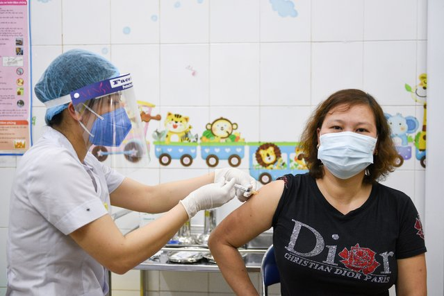 A woman receives a vaccine as Vietnam starts its official rollout of AstraZeneca's coronavirus disease (COVID-19) vaccine for health workers, at Hai Duong Hospital for Tropical Diseases, Hai Duong province, Vietnam, March 8, 2021. (Photo by Thanh Hue/Reuters)