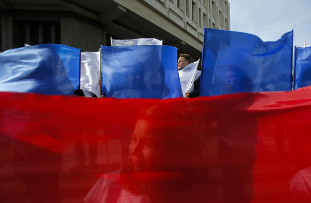 People hold banners in Russia's national flag colors during a meeting to celebrate the first anniversary of Russia's annexation of Ukraine's Black Sea peninsula of Crimea, in central Simferopol March 16, 2015. (Photo by Maxim Shemetov/Reuters)