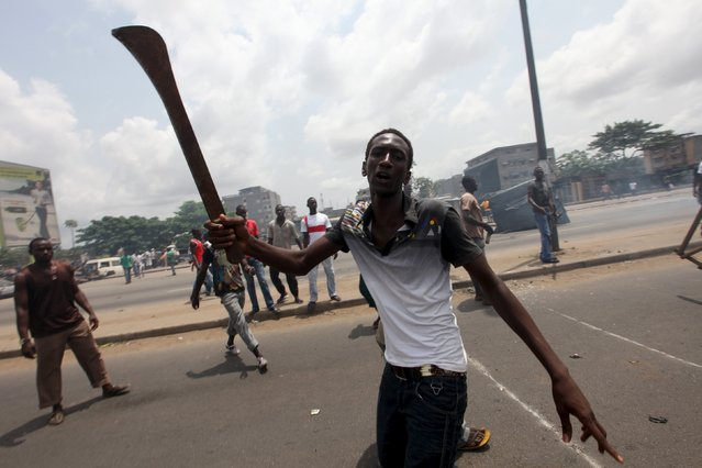 Anti-Gbagbo protester holds a machete near a roadblock and burning tyres in the Abobo area of Abidjan March 3, 2011. The trial of Laurent Gbagbo on charges of crimes against humanity during post-election violence, in which around 3,000 people were killed, will begin on January 28, 2016 at the International Criminal Court. (Photo by Luc Gnago/Reuters)