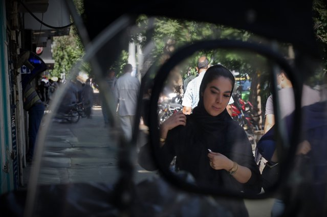 A young Iranian woman walks in Tehran on June 14, 2021, ahead of the June 18 presidential elections. Iran is gearing up for a presidential election on June 18 but many young people are more focussed on the daily struggle to survive and their dreams for the future. Jobs are scarce in a recession-hit economy battered by sanctions, a crisis exacerbated by the region's worst outbreak of the Covid pandemic. (Photo by Atta Kenare/AFP Photo)
