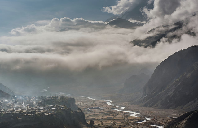 """Keith Urry, March winner. """"As we were leaving the Manang valley, Nepal, early in the morning I looked back to see this gorgeous light over the valley and got this shot before the scene changed"""". MICK RYAN, JUDGE: Zoom lenses should be used more often for landscape photography, rather than just the usual wide-angle lenses. In this stunning photograph the scene is compressed with a zoom lens bringing the distant mountains nearer to add great contrast of scale to the village on the rocky mesa. Add a serpentine river, low clouds and you have a powerful winning photograph. (Photo by Keith Urry/The Guardian)"""