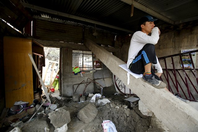A man stands inside his destroyed house after a massive landslide in Chosica, March 24, 2015. (Photo by Mariana Bazo/Reuters)