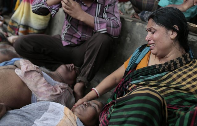 A Bangladeshi Hindu devotee Sapna Das cries as she holds the body of a relative who was killed in a stampede in Langalbandh, 20 kilometers (12 miles) southeast of capital Dhaka, Bangladesh, Friday, March 27, 2015. Local police chief Nazrul Islam said the stampede took place in a Hindu pilgrimage spot on the banks of the Brahmaputra river during an annual religious bathing ritual. (Photo by A. M. Ahad/AP Photo)