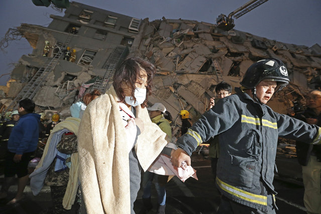 A woman is led by a rescue worker from the site of a toppled building after an earthquake in Tainan, Taiwan, Saturday, February 6, 2016. A 6.4-magnitude earthquake struck southern Taiwan early Saturday, toppling at least one high-rise residential building and trapping people inside. Firefighters rushed to pull out survivors. (Photo by AP Photo)