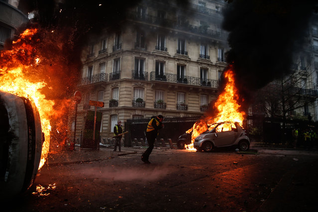 Protesters walk by burning cars during clashes with riot police on the sideline of a protest of Yellow vests (Gilets jaunes) against rising oil prices and living costs, on December 1, 2018 in Paris. (Photo by Abdulmonam Eassa/AFP Photo)