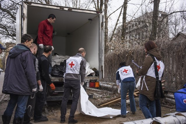 International Committee of the Red Cross (ICRC) workers prepare bags with bodies of government soldiers to be handed over in Donetsk, eastern Ukraine, Friday, March 27, 2015. Separatists in eastern Ukraine have handed over the bodies of 22 government soldiers killed during the fierce, months-long battle over the airport near the rebel stronghold of Donetsk.  (Photo by Mstyslav Chernov/AP Photo)
