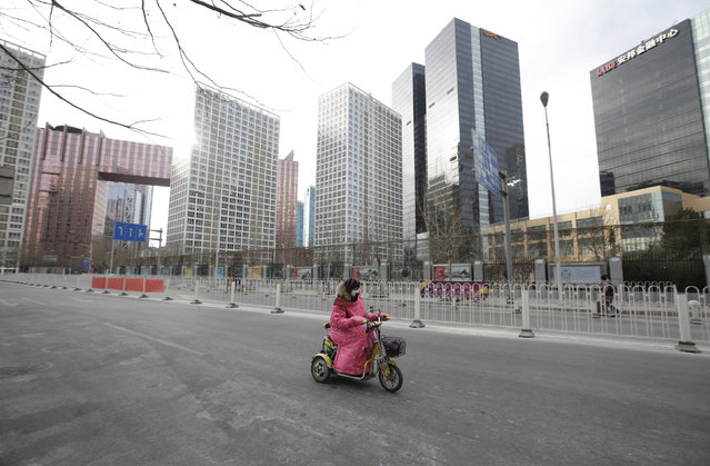 A woman drives a motorbike past office buildings in Beijing's central business district on the eve of the Chinese Lunar New Year, in Beijing, China, February 7, 2016. (Photo by Jason Lee/Reuters)