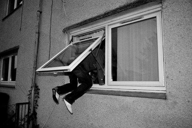 A man climbs into a flat through a front window in Easterhouse. (Photo by Brian Anderson)