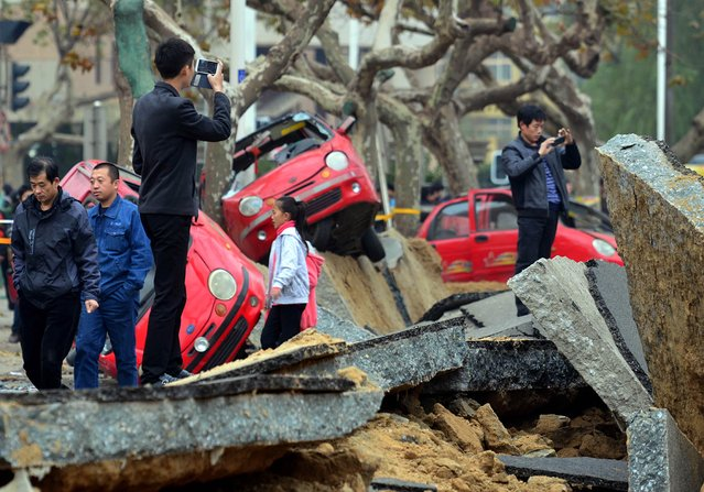 This picture taken on November 24, 2013 shows passersby taking photos at the scene of the damage after an oil pipeline exploded, ripping roads apart, turning cars over and sending thick black smoke billowing over the city of Qingdao, east China's Shandong province on November 22. (Photo by AFP Photo)
