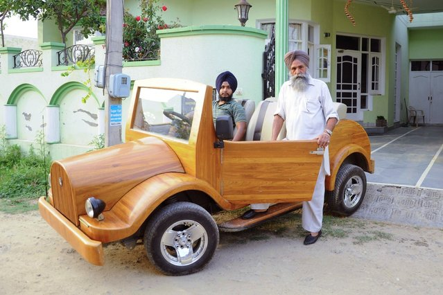 Indian carpenter Mohinder Singh Lotay (R) poses with his son Amandeep Singh Lotay and their handmade five seater wooden car at their home in Patiala on April 1, 2015. They claim the car which cost Indian Rupees 400,000 (USD 6,400) to make and is based on the engine of a Maruti 800 with teak bodywork can attain a top speed of 120kms per hour and has an economy level of 16kms per litre. (Photo by AFP Photo/Stringer)