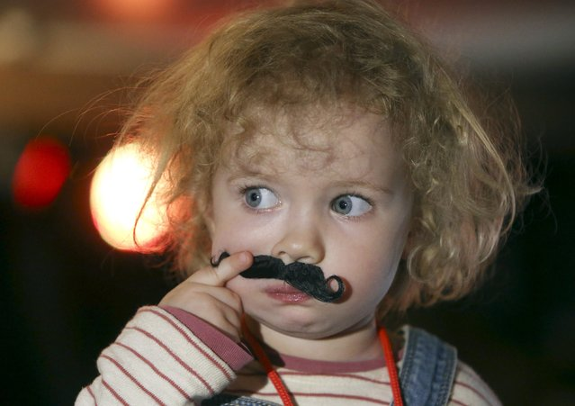 A child attends the 3rd Russian Beard and Moustache Championships in Moscow April 4, 2015. Participants are judged in seven various categories depending on the length and type of moustache and beard, according to organizers. (Photo by Sergei Karpukhin/Reuters)