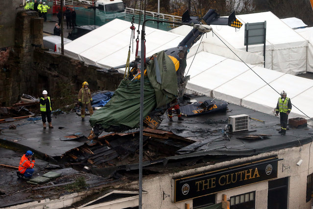 Scottish Fire and Rescue services look on at the helicopter being lifted from the scene Monday, December 2, 2013, following the helicopter crash at the Clutha Bar in Glasgow, Scotland. Scottish emergency workers were sifting through wreckage over the weekend for survivors of a police helicopter crash onto a crowded Glasgow pub that has killed nine people and injured more than two dozen. (Photo by AP Photo)