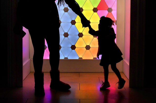 Jasmine White and her daughter Hope, 2, enter one of the four selfie cubes at The Mall in Columbia, Md. on October 25, 2018. The cubes offer changing colorful light patterns and sounds, and shoppers are encouraged to dance and take photos in it. (Photo by Michael S. Williamson/The Washington Post)