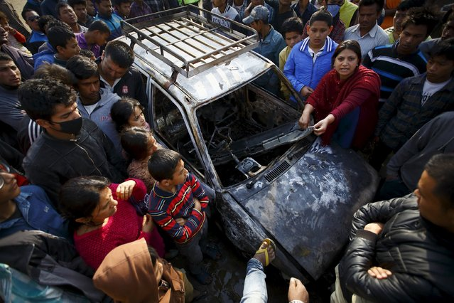 People gather around a taxi burnt by protesters during a nationwide strike organised by the opposition alliance led by the Unified Communist Party of Nepal (Maoist), to demand the new constitution be drafted with the consensus of all political parties, in Kathmandu April 7, 2015. (Photo by Navesh Chitrakar/Reuters)
