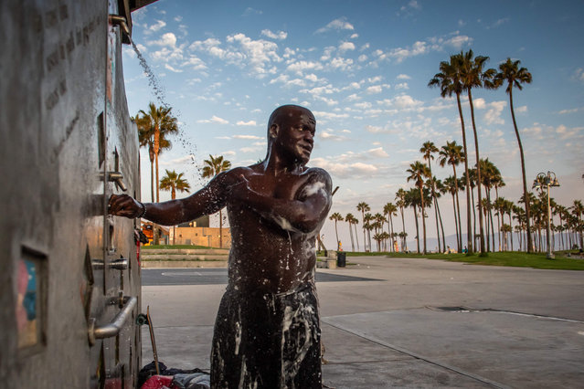 Jamal (only first name given) who has lived on the streets for 18 years, takes a shower in a public beach shower in Venice,California on August 12, 2021. (Photo by Apu Gomes/AFP Photo)