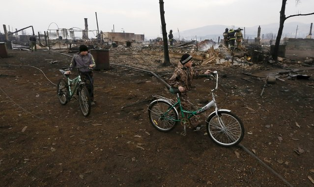 Boys hold bicycles near the debris of burnt buildings in the settlement of Shyra, damaged by recent wildfires, in Khakassia region, April 13, 2015. (Photo by Ilya Naymushin/Reuters)