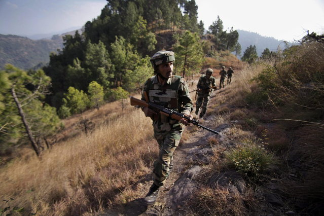 In this Monday, December 23, 2013 photo, Indian army soldiers patrol near one of their forward post at the Line of Control (LOC), that divides Kashmir between India and Pakistan, at Krishna Ghati (KG Sector) in Poonch, 290 kilometers (180 miles) from Jammu, India. (Photo by Channi Anand/AP Photo)