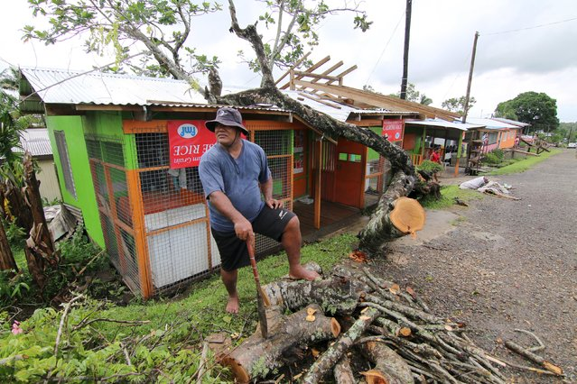 A shopkeeper chops up a tree that had fallen on his roof during Cyclone Winston, as a cleanup continues in the aftermath of the storm in Fiji's capital Suva, February 22, 2016. (Photo by Steven Saphore/Reuters)