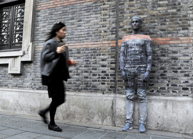 A woman walks past a man blending himself into the background by covering his body with paint, in front of the wall of an ancient building in Shanghai, April 10, 2015. (Photo by Reuters/Stringer)
