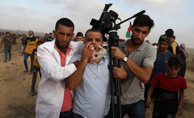 Medics and protestors evacuate a wounded of cameraman of Asem Shehada, from the fence of Gaza Strip border with Israel, during a protest marking the anniversary of a 1969 arson attack at Jerusalem's Al-Aqsa mosque by an Australian tourist later found to be mentally ill, east of Gaza City, Saturday, August 21, 2021. (Photo by Adel Hana/AP Photo)