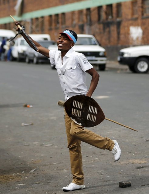 A local gestures as he holds a stick and a shield outside a hostel during anti-immigrant related violence in Johannesburg, April 17, 2015. (Photo by Siphiwe Sibeko/Reuters)