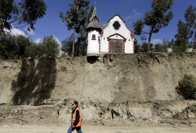 A worker walks in front of a chapel after a landslide caused by heavy rain in Jupapina, on the outskirts of La Paz, Bolivia February 29, 2016. (Photo by David Mercado/Reuters)