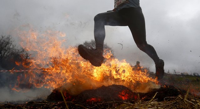 A competitor jumps across a burning obstacle during the Tough Guy event in Perton, central England January 26, 2014. (Photo by Darren Staples/Reuters)