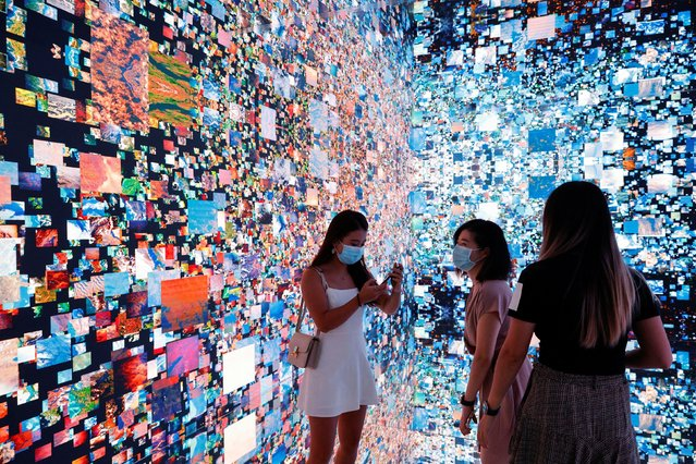 """Visitors are pictured in front of an immersive art installation titled """"Machine Hallucinations – Space: Metaverse"""" by media artist Refik Anadol, which will be converted into NFT and auctioned online at Sotheby's, at the Digital Art Fair, in Hong Kong, China on September 30, 2021. (Photo by Tyrone Siu/Reuters)"""