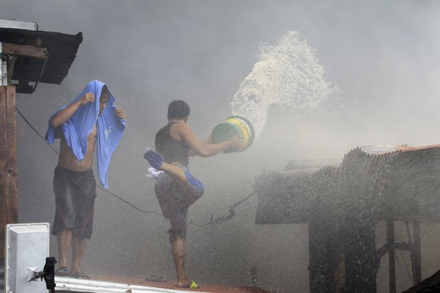 A resident splashes a pail of water on charred houses after a fire razed through residential area in San Andres Bukid, metro Manila March 12, 2016. (Photo by Romeo Ranoco/Reuters)