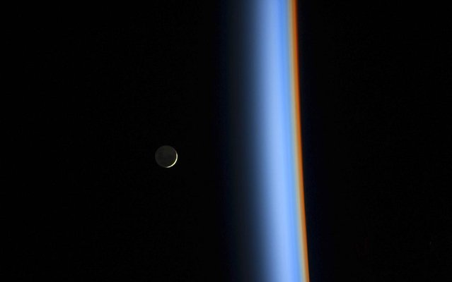 A crescent moon rises over the cusp of the Earth's atmosphere in this picture by Japan Aerospace Exploration Agency astronaut Koichi Wakata onboard the International Space Station taken February 1, 2014. Distinct colors are visible because the dominant gases and particles in each layer of the atmosphere act as prisms, filtering out certain colors of light. (Photo by Koichi Wakata/Reuters/NASA)
