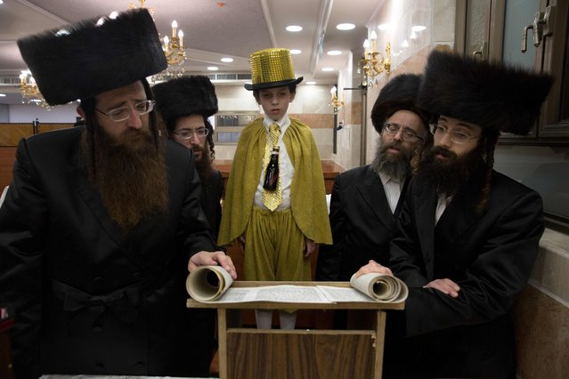 Ultra-Orthodox Jews and a dressed up boy read the book of Esther at a synagogue in the Israeli city of Beit Shemesh on March 23, 2016 during the feast of Purim. The carnival-like Purim holiday is celebrated with parades and costume parties to commemorate the deliverance of the Jewish people from a plot to exterminate them in the ancient Persian empire 2,500 years ago, as recorded in the Biblical Book of Esther. (Photo by Menahem Kahana/AFP Photo)