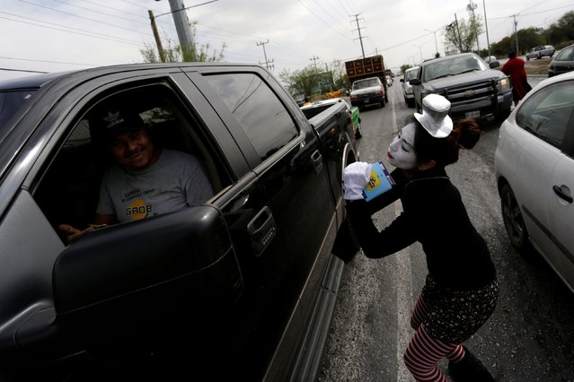 A mime artist gestures to a driver that refused to wear the seatbelt at a traffic light as part of a government programme to raise awareness among motorists and pedestrians to respect transit rules, in the municipality of Garcia, on the outskirts of Monterrey, Mexico February 14, 2017. (Photo by Daniel Becerril/Reuters)