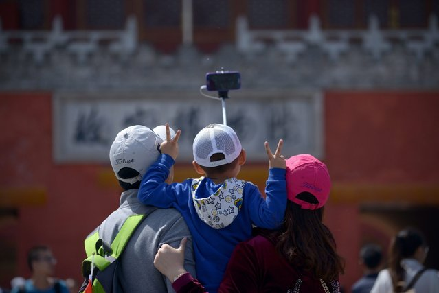 A family uses a selfie stick to take a photo after visiting the Forbidden City in Beijing on May 3, 2015. (Photo by Wang Zhao/AFP Photo)