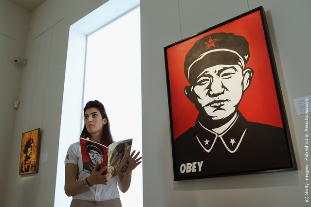 A Bonhams intern stands beside a work entitled 'Chinese Soldier' by Shepard Fairey