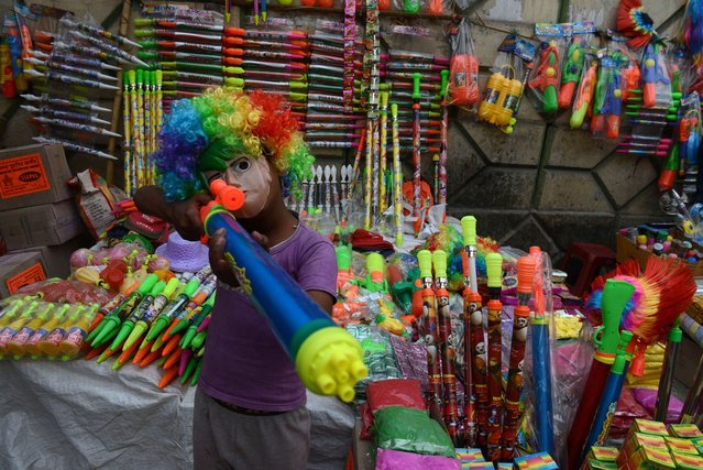 An Indian child, the son of a street vendor, poses at a stall selling water guns for the upcoming Hindu festival of Holi in Siliguri on March 13, 2014. Holi, the popular Hindu spring festival of colours is observed in India at the end of the winter season on the last full moon of the lunar month and will be celebrated on March 16 this year. (Photo by Diptendu Dutta/AFP Photo)