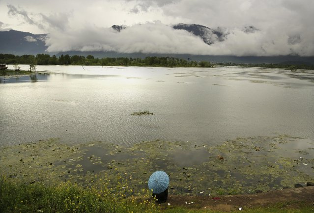 A Kashmiri man holds an umbrella as he fishes sitting on the banks of the Nigeen Lake on a rainy day in Srinagar, Indian controlled Kashmir, Monday, April 27, 2015. (Photo by Mukhtar Khan/AP Photo)