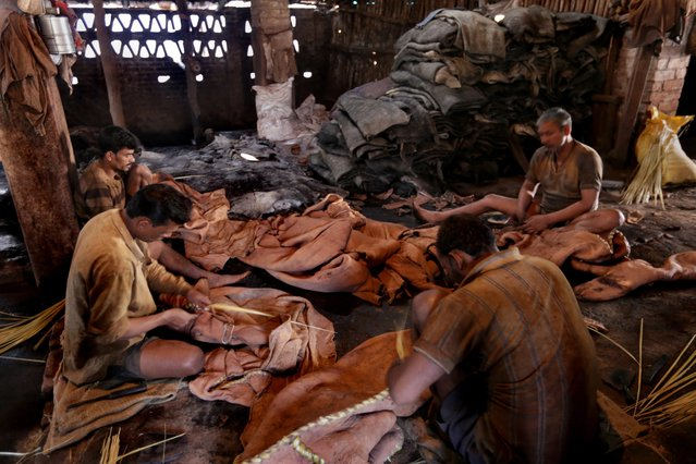 Indian laborers stitch buffalo leather at a tannery workshop in Calcutta, eastern India, 17 February 2014. (Photo by Piyal Adhikary/EPA)