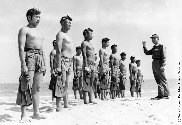 A line of Nationalist Chinese Frogmen, who form the 'Silent Service' of the Quemoy Defence Command, wearing army shorts and holding pairs of fins are briefed by one of their commanding officers on a Quemoy beach