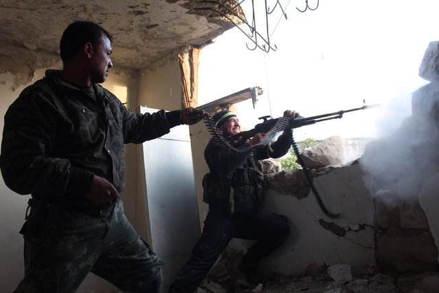 Rebel fighters fire a machine gun during clashes with pro-government forces on March 18, 2014 in the northern Syrian city of Aleppo. The regime planes bombed Aleppo today, killing at least four people, including two children, according to the Syrian Observatory for Human Rights. (Photo by Tamer Al-Halabi/AFP Photo)
