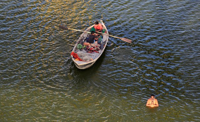 Boys paddle a boat as a Hindu man prays in the waters of the river Ganges in Allahabad, India, April 13, 2016. (Photo by Jitendra Prakash/Reuters)