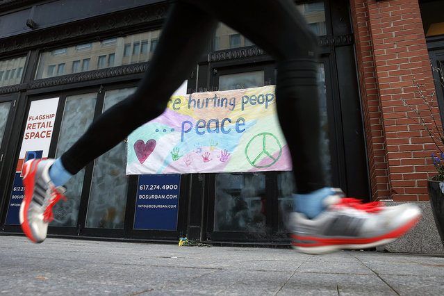 """A runner passes the site of the second detonation on the third anniversary of the Boston Marathon bombings, Friday, April 15, 2016, in Boston. Throughout the day, residents will be taking part in blood drives, food and clothing collections and other community service projects as the city has proclaimed April 15 """"One Boston Day"""", a day to celebrate the city's resilience through acts of kindness and generosity. (Photo by Michael Dwyer/AP Photo)"""