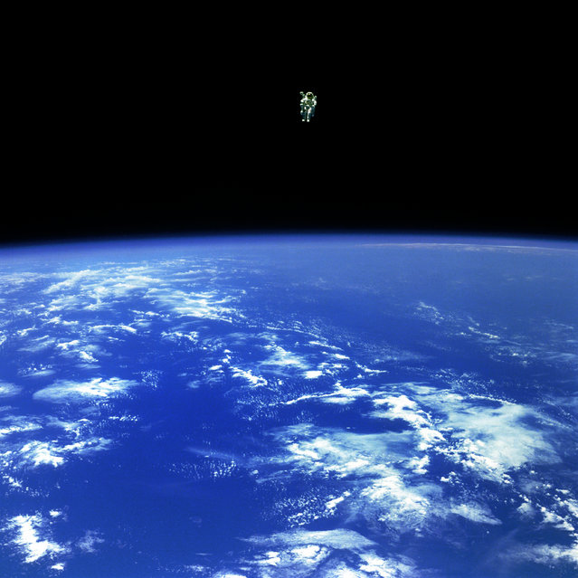 "Mission Specialist Bruce McCandless II, is seen further away from the confines and safety of his ship than any previous astronaut has ever been. This space first was made possible by the Manned Manuevering Unit or MMU, a nitrogen jet propelled backpack. After a series of test maneuvers inside and above Challenger's payload bay, McCandless went ""free-flying"" to a distance of 320 feet away from the Orbiter. This stunning orbital panorama view shows McCandless out there amongst the black and blue of Earth and space. (Photo by NASA)"