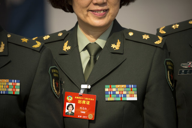 In this Friday, March 3, 2017 photo, a military delegate poses for a group photo as she arrives for of the opening session of the Chinese People's Political Consultative Congress (CPPCC) at the Great Hall of the People in Beijing. (Photo by Mark Schiefelbein/AP Photo)