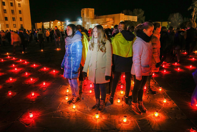 """Ukrainians light candles near the memorial for """"liquidators"""" who died during cleaning up works after the Chernobyl nuclear power plant disaster, during a ceremony in Slavutich city, some 190 km north of the capital Kiev, Ukraine, early 26 April 2016. In the early hours of 26 April 1986 the Unit 4 reactor at the Chernobyl power station blew apart. Facing nuclear disaster on unprecedented scale Soviet authorities tried to contain the situation by sending thousands of ill-equipped men into a radioactive maelstrom. (Photo by Sergey Dolzhenko/EPA)"""