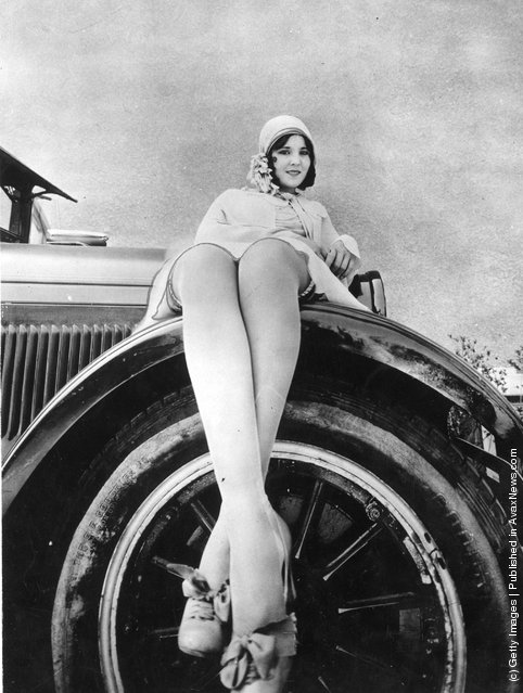 1925: South American film star Raquel Torres poses sitting on the wheel of a car with her legs enlarged by the camera angle